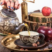 32790921 - woman pouring tea from teapot on vintage wooden table with hazelnuts apples and golden coffee mill in traditional style