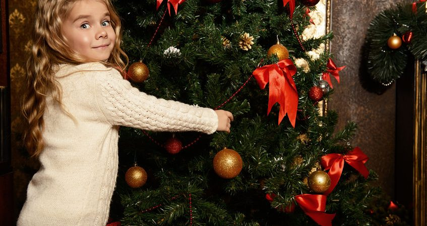 49798606 - angelic little girl decorating christmas tree with balls.